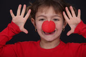 Little girl with red nose playing clown — Stock Photo