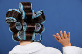 Back view of a woman wearing rollers and waving — Stock Photo