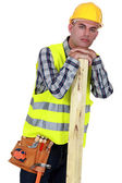 A carpenter leaning one a piece of wood. — Stock Photo