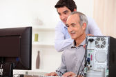 Young man teaching an elderly man computer skills — Stock Photo
