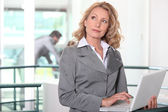 Businesswoman at workplace with laptop — Stock Photo