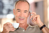 Grey haired man drinking coffee and speaking on mobile telephone — Stock Photo