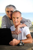Elderly couple with a computer — Stok fotoğraf
