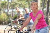 Groep van senioren paardrijden fietsen in het park — Stockfoto