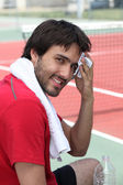 Tennis player mopping his brow on the sidelines — Stock Photo