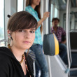 Photo of teenager riding the tram with passenger in background - Stock Photo