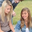 Students sitting in a park — Stockfoto