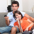 Young couple at home, watching TV and talking on the telephone — Stock Photo