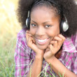 Stock Photo: Black womhearing music through headphones