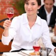 Young woman in a restaurant raising a glass of rose wine — Stock Photo #7659897