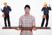 Man balancing tiny workers on plank of wood — Stock Photo