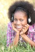 Black woman hearing music through headphones — Stock Photo