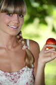 Young and beautiful woman holding a nectarine — Stock Photo