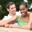 Stock Photo: Mixed race couple cuddling in countryside