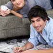 Couple reading newspaper at home - Stock Photo