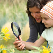 Mother and daughter looking at a flower with a magnifying glass — Stok fotoğraf