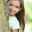 Young girl hiding behind a tree — Stock Photo #7661100