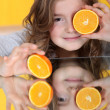 A little girl with an orange cut in half. — Stock Photo