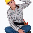 Tradeswoman touching the brim of her hat - Stock Photo