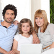 Parents and daughter sat on settee — Stock Photo