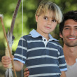 Father learning his son how to draw a bow — Stock Photo