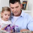 A father reading to her daughter. — Stock Photo