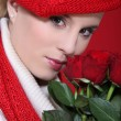 Portrait of gorgeous blonde with red roses and assorted clothes — Stock Photo