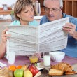 Couple reading newspaper over breakfast — Stock Photo #7663757