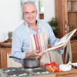 Stock Photo: Mpreparing meal with help of cookbook