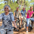 Senior woman and her friends riding bikes through the countryside — Stock Photo