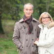 Stock Photo: Elderly couple walking through woods