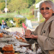 A senior woman  in an open-air market - Stock Photo
