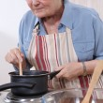 Senior woman cooking — Stock Photo