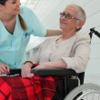 Nurse talking to an elderly lady in a wheelchair — Stock Photo