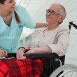 Nurse talking to elderly lady in wheelchair — Stock Photo #7664475