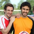 Stock Photo: Three young football players on a football field.