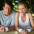 Sporty couple having a rest from exercise in the country — Stock Photo