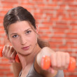 Young woman using hand weights in front of a red brick wall — Stock Photo #7665146
