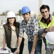 Stock Photo: Team of tradespeople discussing blueprint