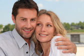 Head and shoulders of couple in tight embrace by the water — Stock Photo