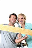 Couple holding colorful wallpaper border — Stock Photo