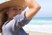 Woman holding onto her straw hat in a breeze — Stock Photo