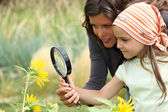 Mother and daughter looking at a flower with a magnifying glass — Stock Photo