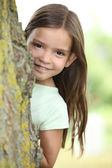 Young girl hiding behind a tree — Stock Photo