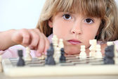 Serious little girl playing chess — Stock Photo