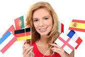 Chica sosteniendo un montón de banderas nacionales — Foto de Stock