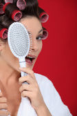 Woman with hair curlers holding a brush — Stock Photo
