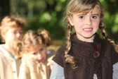 Three little girls in the park in autumn — Stock Photo