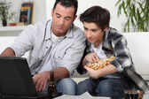 A father and son about to watch a game on a computer. — Stock Photo