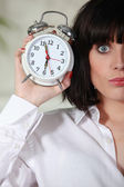 Woman with tousled hair holding alarm clock — Stock Photo